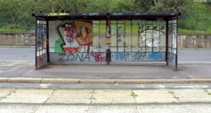A bus stop showing the walls full of graffiti